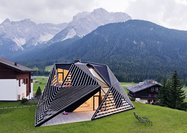 This slatted structure by architects Plasma Studio looks like it's crawling over an apartment building in the Italian Dolomites