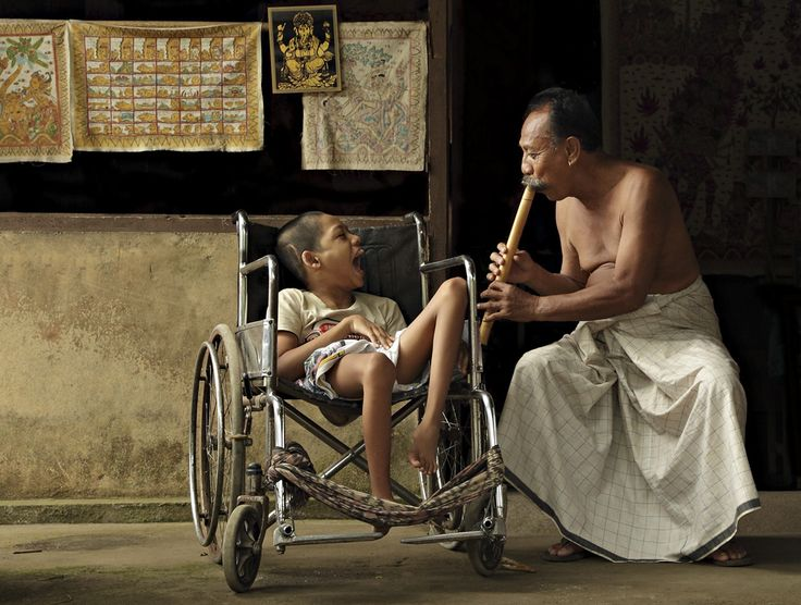 The Music Of Love. This picture was taken in Tenganan Village, Bali (2010). Tenganan is the most famous Bali Aga (original Balinese) village and is located close to Candi Dasa in East Bali. A man was playing bamboo music to entertain a disabled child which is not his son, but he loves this child likes he loves his own son. (Photo and caption by Ario Wibisono)