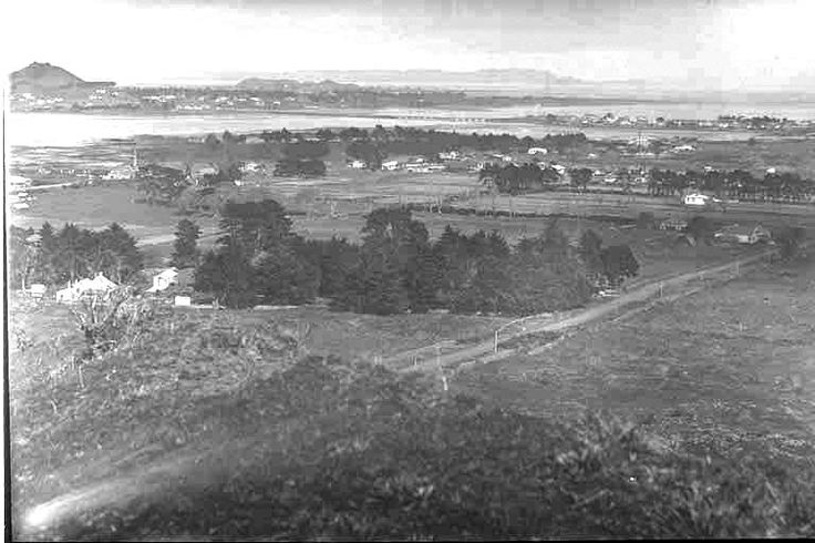 1923. A panoramic view over Te Papapa south west from Mount Smart, with Onehunga (in the foreground), Church Street (diagonal foreground), Manukau Harbour and Mangere Bridge (in the centre), Mangere mountain (far left) and South Auckland (in the background). Sir George Grey Special Collections, Auckland Libraries, 4-4538.