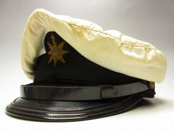 Boy's military style cap with unusual mariner's compass embroidered insignia. The cap still has it's original protective white cover suggesting it may have been worn by a  naval/maritime safety agency cadet. The Japanese Maritime Safety Agency was formed in 1948 and used the compass as it's logo. Now it is known as Japan Coast Guard.