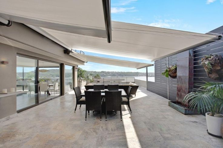 Motorised Rainproof Retracting Awnings provide rain and sun protection for this exposed large terrace