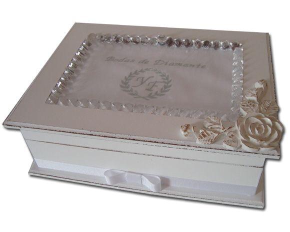 """Que tal um presente para marcar esta data tão especial? Sugerimos esta linda caixa de chá de mdf pintada de branco com acabamento rústico (lixada nas extremidades). Por baixo do vidro da tampa colocamos um tecido, onde é bordado """"Bodas de Diamante"""" e um brasão com as iniciais do casal, para finalizar contornamos a peça com mini diamantes de acrílico e um laço de gorgorão branco na base. Possui seis divisórias.   Possíveis variações: produtos artesanais podem apresentar pequenas variações de…"""