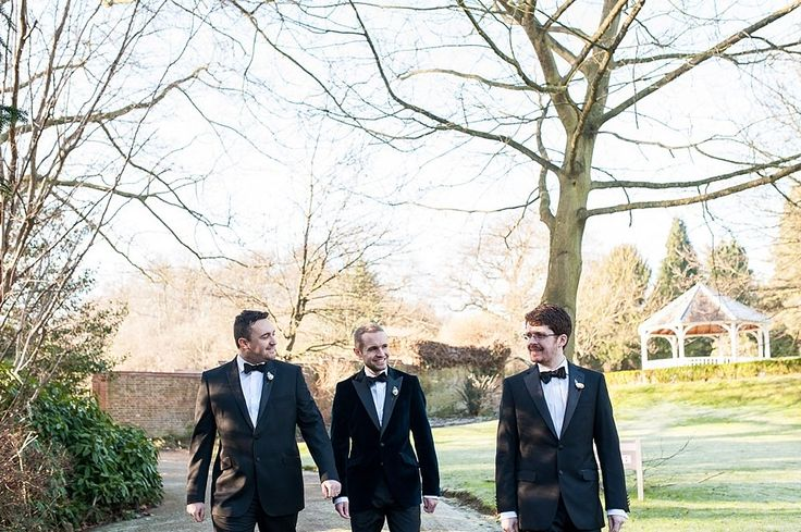 Gorgeous groom in black tie with ushers walking to his wedding at Rowhill Grange Hotel in Kent. © Fiona Kelly Photography
