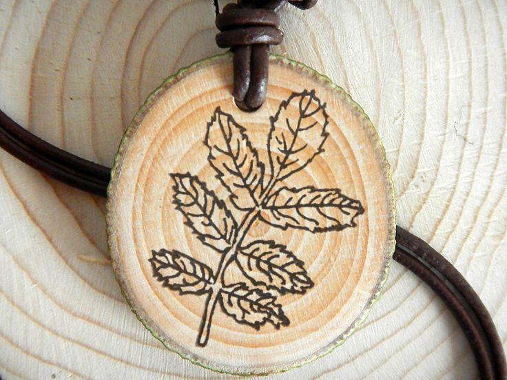 Amulett aus heimischem Astholz aus der Region mit einem durch Brandmalerei verziertem Ebereschenblatt-Motiv.