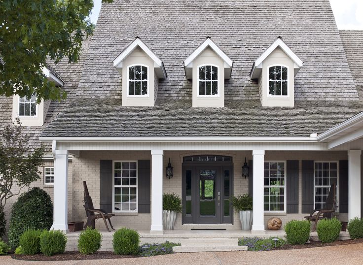 At the home of I.O. Metro founder and chief executive officer Jay Howard and his wife, Christine, the company's creative director, benches on the front porch are repurposed ox carts from India . The home's exterior was updated with Sherwin-Williams paint: Tony Taupe on the brick, Black Fox on shutters and doors, and Pure White on columns.