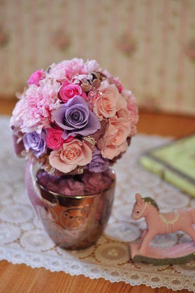 かわいさ溢れるフェミニンピンクのトピアリー。 プリザーブドフラワーカーネーションをメインに、大きなリボンとピンク・パープルのローズをアレンジ。いつまでも綺麗で若々しくいて欲しい、ピンクが大好きな大人かわいいお母様におすすめです。