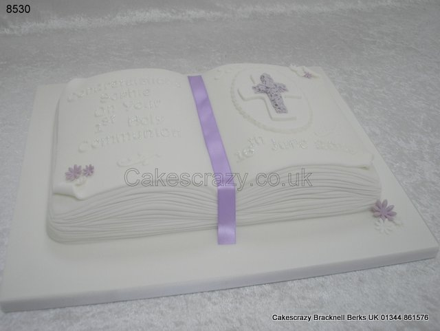 Open book shaped communion cake with lilac sugar cross mounted on a sugar plaque, lilac and white daisies, scolls and glitter message