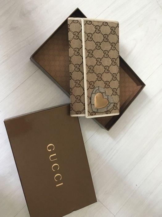 Portefeuille Gucci toile imprimée  femme en tres bon état  Intérieur nickel  Seul petit défaut quelques rayures sur le dor...