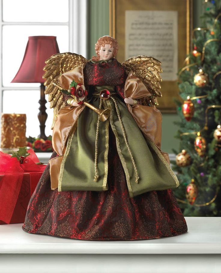 Deck your tree with this gorgeous angel tree topper! Shes draped in rich robes of burgundy brocade, green and gold that will shimmer and shine in the light. She has sparkling golden wings with delicat