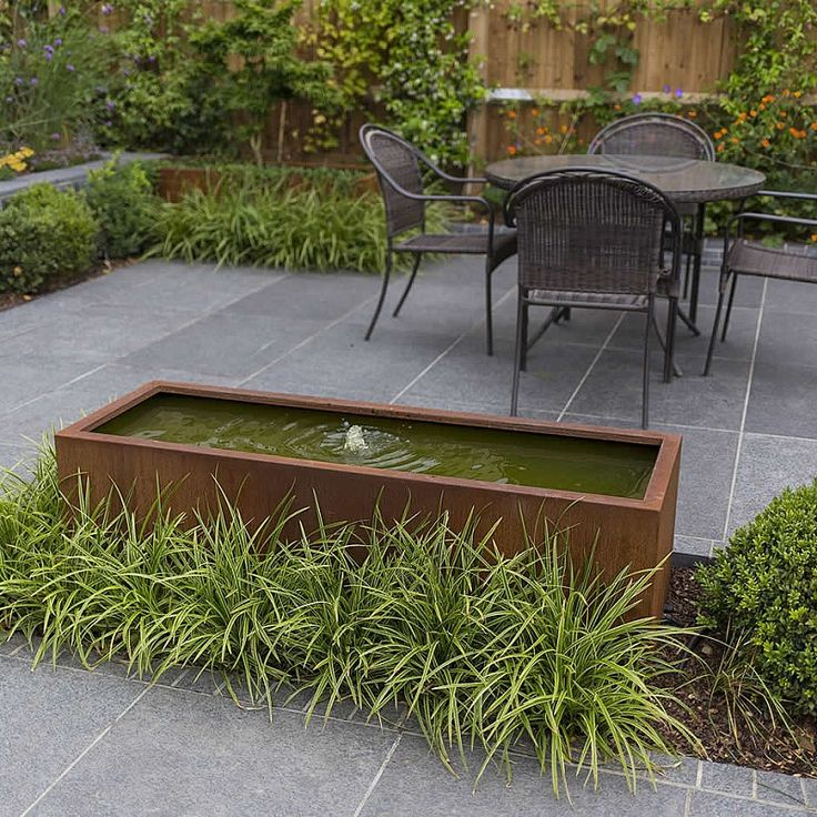 Corten steel trough with small bubbling fountain - blends into patio with Carex planting.