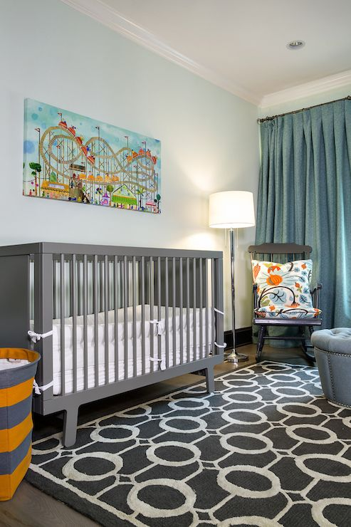 Blue and gray baby boy's nursery with roller coaster canvas over a gray Babyletto Hudson Crib with orange and gray rugby striped basket to the left atop a gray and white chain link rug layered over hardwood floors.