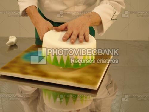 Mãos pasta americana no bolo | PHOTOVIDEOBANK imagens de confeiteiro preparando ao confeitar bolos com pasta americana confeitaria de bolos para festas, foto com pessoa bolo branco no prato grande azulejo na mesa da cozinha aço inox espelhado