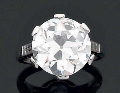 Bague en platine ornée d'un diamant de taille brillant épaulé de deux diamants baguettes. Diamant accompagné d'un certificat du Laboratoire francais de gemmologie datant de 1994 et précisant Poids: 7.78… - Aguttes - 14/06/2012