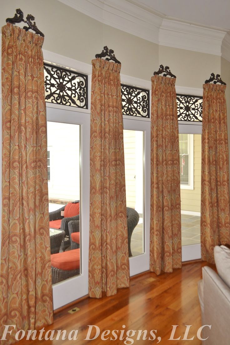 beautiful bay window treatment includes tableaux faux iron in the transoms with stationary drapery panels on wrought iron brackets