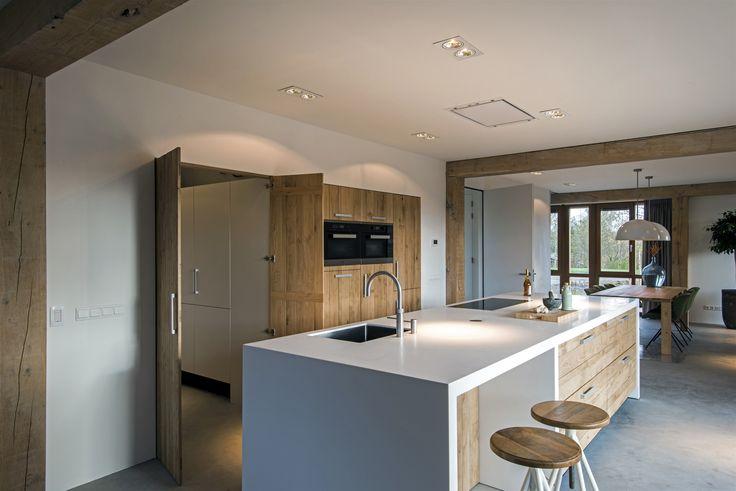 Houten keuken van ruw eiken met groot kookeiland. In de houten kastenwand met inbouwapparatuur zijn ook houten deuren als ingang naar de bijkeuken geïntegreerd. Via JP Walker
