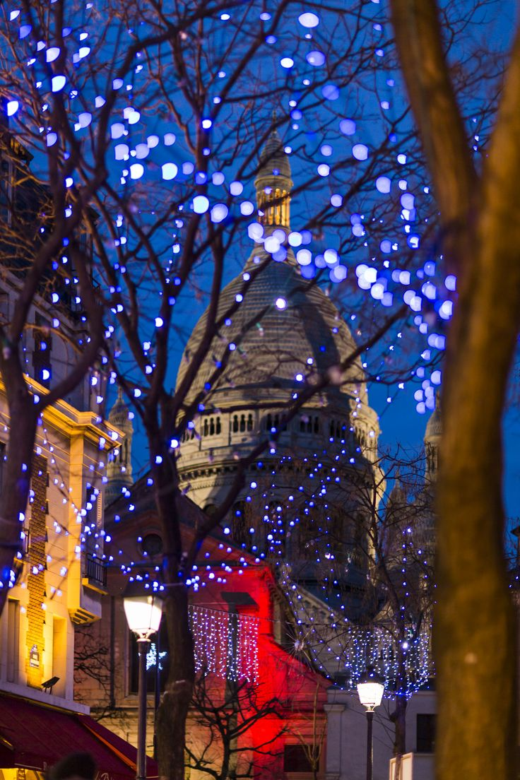 Christmas lights in Montmartre, Paris, Place du Tertre with the Sacre Coeur in the background.