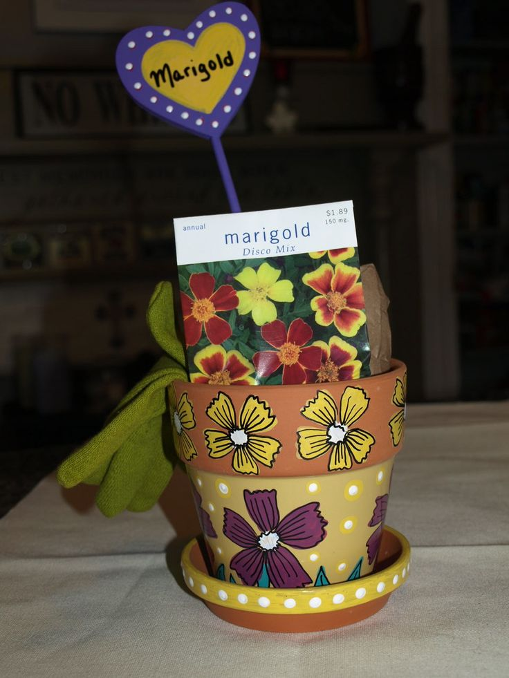Hand painted flower pot. I used acrylic paints and enamel paint pens. I tucked in gloves, seeds, and organic soil.