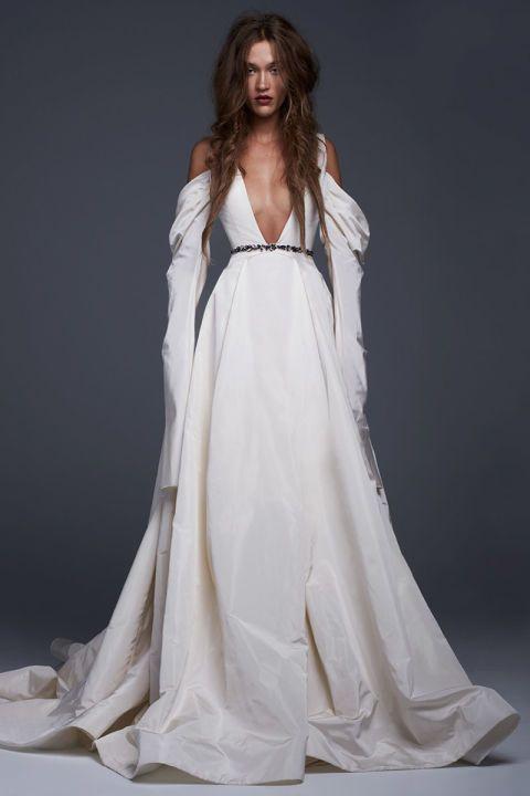 Avorio per questo abito da sposa in seta con profondo scollo a V, maxi gonna e maniche drappeggiate. Ficus on: la cintura gioiello.