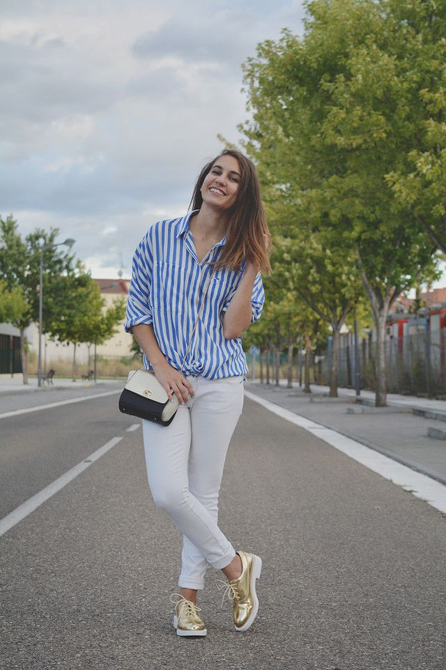 Camisa de rayas combinada con pantalón blanco y accesorios en dorado