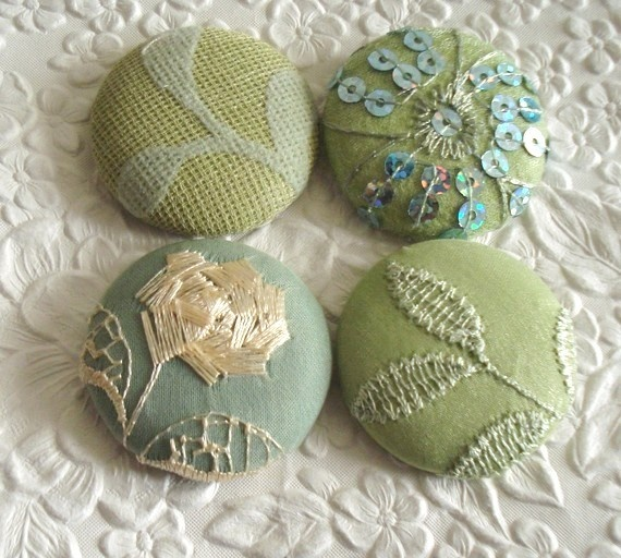 Fabric covered embroidered buttons.