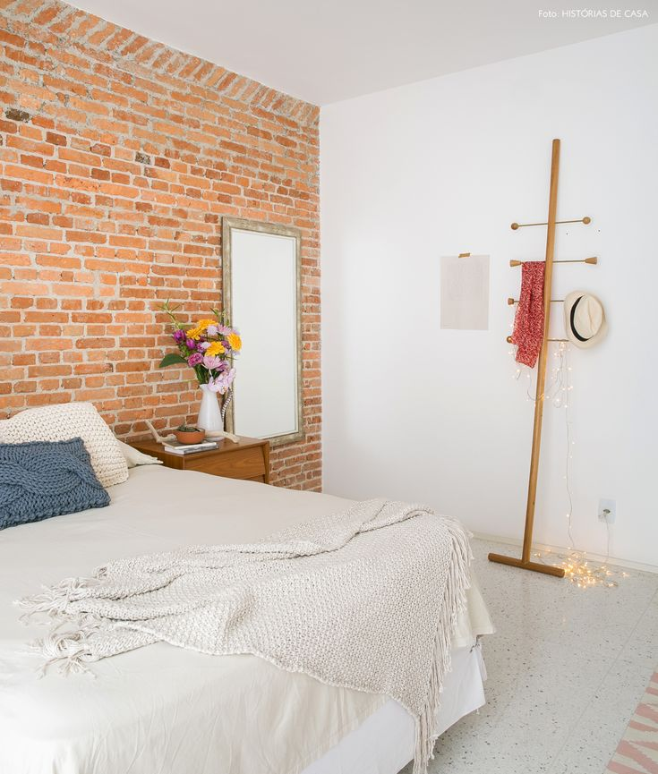 quarto aconchegante com parede de tijolinho, piso branco e cabideiro de design assinado - matéria em parceria com a boobam.com.br