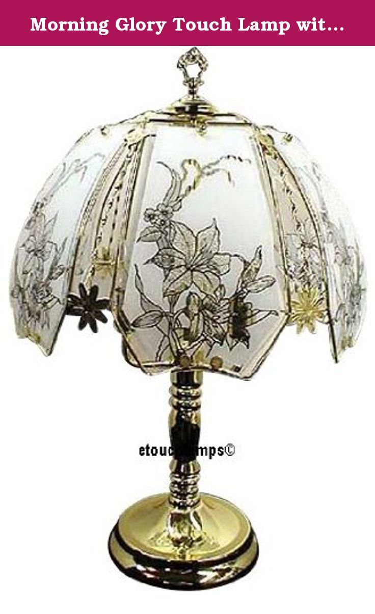 """Morning Glory Touch Lamp with Polished Brass Base. This is a great design of our Morning Glory touch lamps. Standing 23"""" tall the base of this touch lamp has a Polished Brass finish. The diameter of the shade is 14 inches so this is a nice-size lamp. Touching the base anywhere turns the lamp on and off and controls the 3 power settings. What makes this lamp so unique, however, is the shade. In a metal framework are 6 panels of glass. Each panel has an image of a morning glory. This lamp…"""
