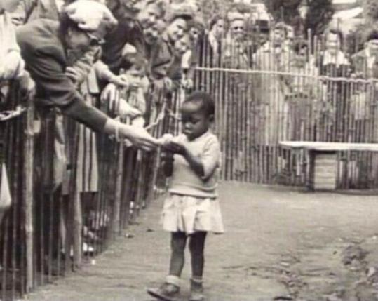 Bambina africana in uno zoo umano, Belgio 1958. - La brava signora sta porgendo una banana alla bambina, come se fosse una scimmia. - I momenti in cui ti vergogni di appartenere al genere umano!