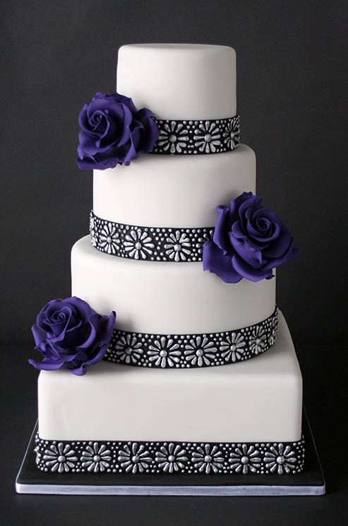 deep purple roses and a black and silver floral pattern glam up this modern white cake