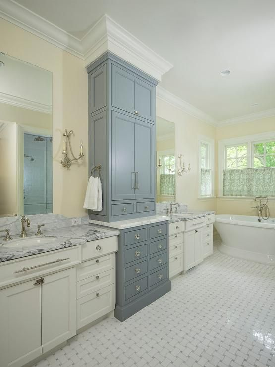 Two-tone bathroom features walls painted cream lined with tall gray linen cabinets flanked by his and hers washstands painted white topped with gray and white marble and tall frameless mirrors illuminated by beaded French sconces alongside a white marble basketweave tiled floor.