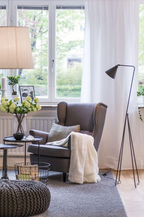 szary fotel uszak,szary dywan,szara dziergana pufa i czarna metalowa lampa podłogowa w salonie