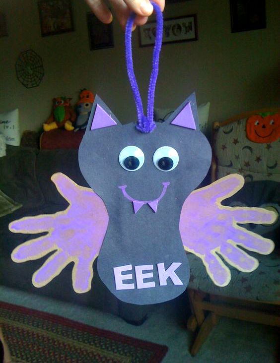 "Make a hanging handprint bat craft with your little ones, it's the cutest Halloween keepsake ever! I found this on Pinterest by Shannon Galvin who wrote how to make it ""Construction paper bat with purple hand prints on cardboard. Googly eyes makes everything adorable, purple painted smile and foam fangs. Pipe cleaner hanger."" Make sure to follow …"