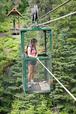 Winner Creek Hand Tram, Girdwood Alaska. Suspended by ropes and pulleys 200 feet above the creek gorge is a steel cage that traverses the distance between the cliffs where hikers can haul themselves from one side to the other.