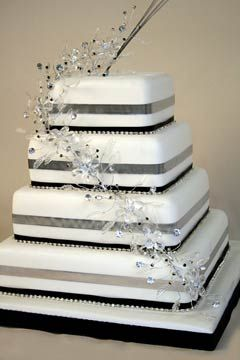 Four tier silver, black and white square wedding cake, decorated with silver and black ribbon and cascading crystal beaded wedding cake topper. From www.thecakestore.co.uk