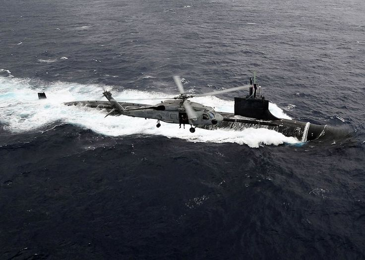US. Navy Seawolf class attack submarine USS Connecticut SSN- 22 and a SH-60F Sea Hawk.