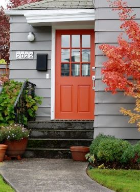 Burnt Orange front door with white trim and Grey weatherboards. This burnt orange coloured front door compliments the colour of the tree foliage and terracotta pots.