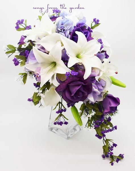 """This cascade bouquet of purple Real Touch roses, Real Touch white Asiatic lilies, lavender silk hydrangea, silk white and purple filler flowers create a lovely custom real touch flower bridal bouquet that can be yours to have and to hold on your wedding day! I can create it for you as shown or customize it to fit your color scheme. We can work together to create a custom silk flower wedding package for your entire wedding party!  This custom silk flower bridal bouquet is 10"""" in diameter ..."""