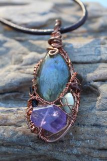 Kitty Carter wrapped this copper pendant as a 5 stone combination.  These are combined to create a balanced piece of crystal jewelry that was created to help the wearer with higher purpose living and rest in their dreams!   *Labradorite is the tear drop stone (middle top) *Dark Green Tourmaline crystal (left side) *Amethyst (bottom center) *Tumbled Green Aquamarine (right side) *Red Garnet (top right)  This Beautiful pendant comes with a brown leather cord necklace or copper chain, your…