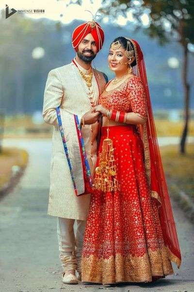 Sikh Brides - Bride in a Red and Gold Lehenga with the Groom in an Offwhite Sherwani with Gold and Pearl Satlada | WedMeGood #wedmegood #indianbride #indiangroom #sikhbride #sikhbrideoutfit #bridal #red #indianwedding #sikhcouple