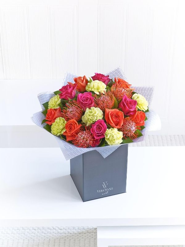 This fresh and vibrant Vera Wang bouquet features colours reminiscent of a tropical sunset. It's an enchanting mix of fiery orange, cerise pink and zesty lime. The addition of leucospermum gives a truly exotic feel to this magnificent hand-tied.