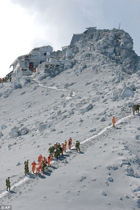 A group of rescuers traverse the volcano slope