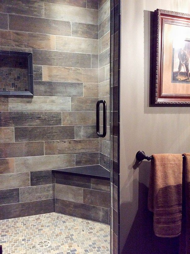 Brown and gray bathroom with a warm rustic vibe - beautiful tile shower with subway pattern and mosaic floor