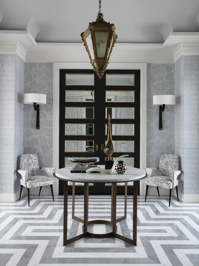 The gray-and-white entrance hall, designed by Jean-Louis Deniot, Inc., features a 17th-century French lantern and a marble floor