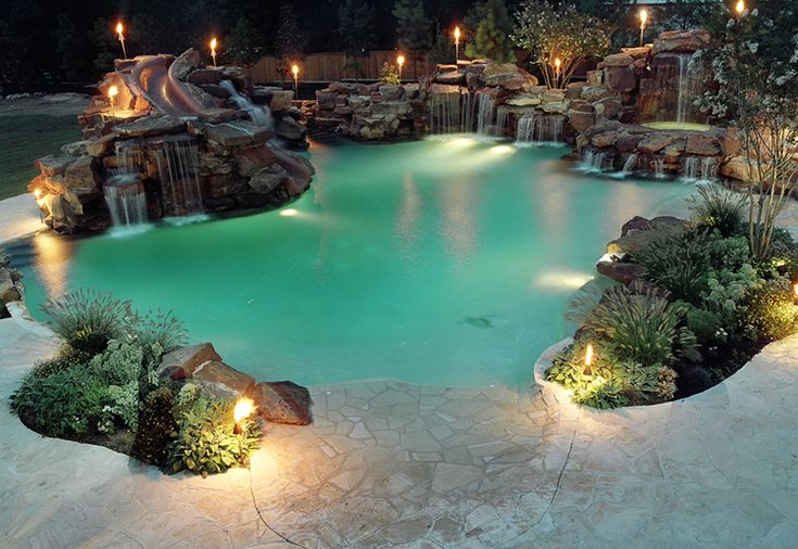 Massive boulder waterfalls, interesting shurbs make nice breaks in decking.  Portfolio page for Atlantis Pools Tulsa Oklahoma inground in ground swimming pool pools builder contractor  not a big fan of the green pool lighting look.