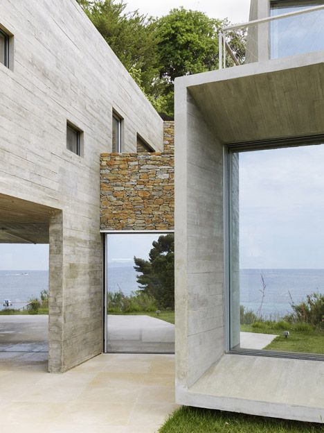 Concrete Maison Le Cap house features mirrored glazing to reflect the seaside scenery
