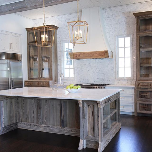 Step into this beautifully rustic cottage kitchen featuring a large distressed oak island finished with white quartzite countertops and fitted with built in shelving plus a sink accented by a polished nickel deck mount faucet illuminated by two Darlana 4 light brass lanterns hung from distressed oak beams.