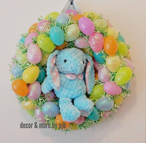"""Hoppy Easter!   Welcome Spring and Easter with this cheerful wreath!  Over 40 colorful eggs, (many of them coated with shimmering glitter), form this lovely handmade wreath! Perfect for your home or office.   Comes with free Bunny stuffed toy. (Not attached. Can be displayed with or without- see images) Please note pink or blue bunny at checkout.   15.5"""" wide by 5.5"""" depth Recommend for indoor display"""