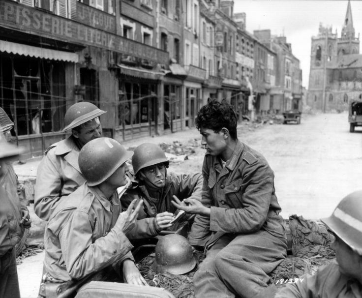 American sapper Private 1st Class Francis Leu and British correspondents John Prince, of The London Times and Philip Grune, of the London Evening Standard talk to a prisoner of the Wehrmacht in the area Ducloux in the French town of La Haye-du-Puits. Background Photo - Cathedral of Saint-Jean