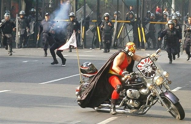 Luchador riding a motorcycle while riot police fire tear gas at him