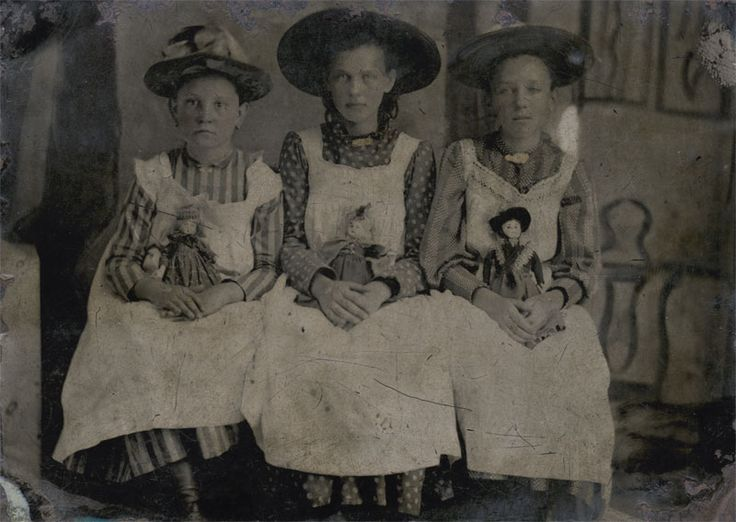 ca. 1870's, [tintype portrait of of three seated young girls holding their dolls] via Charles Schwartz Photography