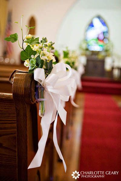 White flowers in miniature vases along the pews
